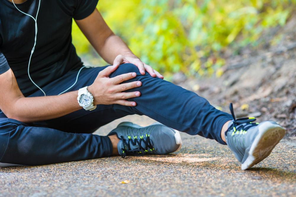 mężczyzna siedzący na chodniku z urazem kolana
