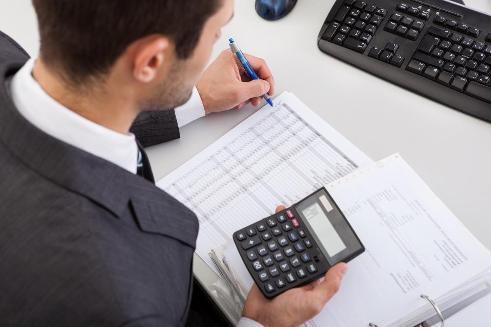 mezczyzna obliczajacy na kalkulatorze w biurze