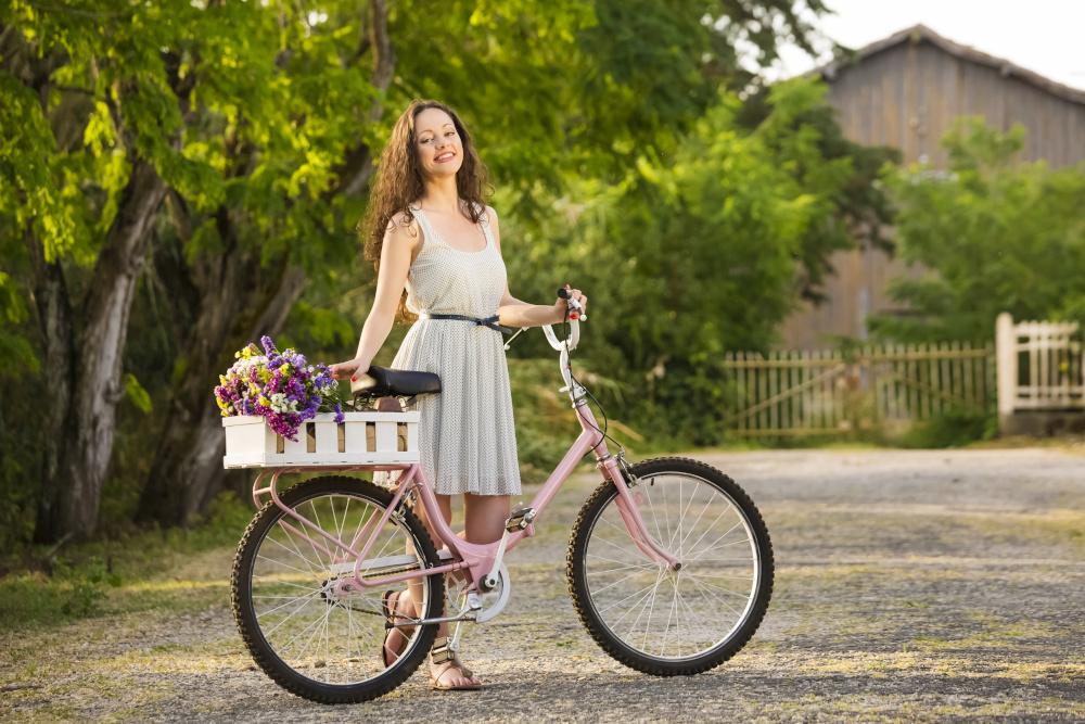 szczesliwa kobieta stojaca przy rowerze w ktorym na bagazniku znajduje sie skrzynka a w niej kwiaty