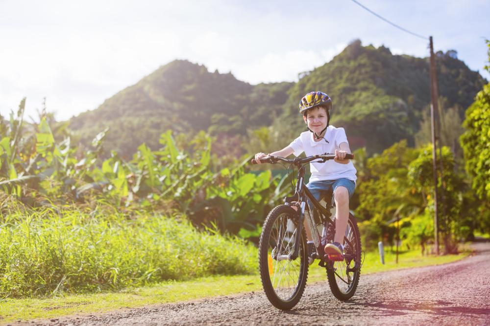 mlody chlopeic na rowerze z kaskiem zna glowie