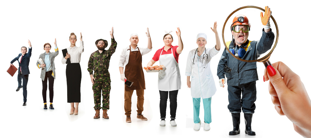 poszukiwania pracowników pracownicy różnych zawodów ustawieni w kolejce obserowany lupą jest pracownik budowlany