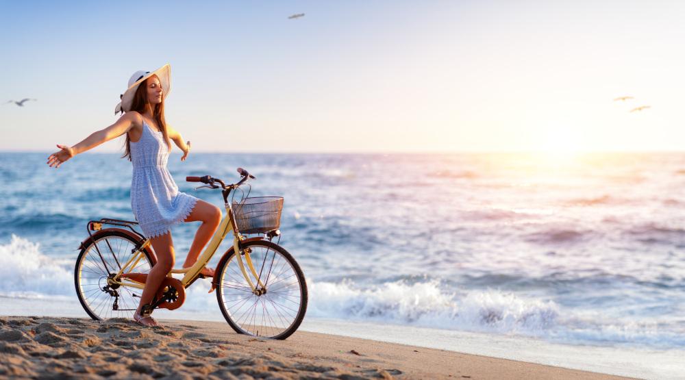 kobieta jeżdżąca na rowerze po plaży